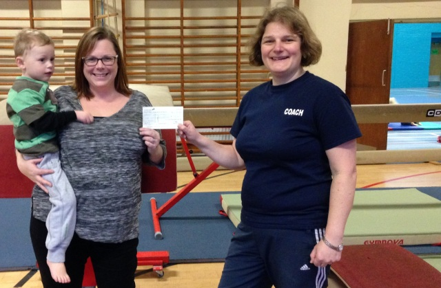Pre-School class parent Katy Glynn and son hand over a cheque for £726 to coach Becca Hamm from MoneySuperMarket